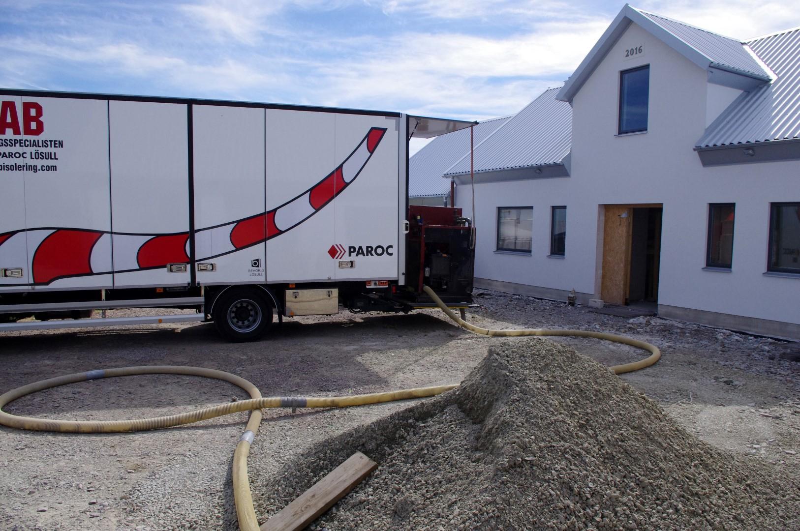 Vom LKW aus wird die Steinwolle durch einen langen Schlauch ins Haus gepustet